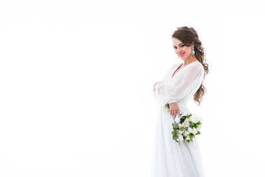 smiling bride posing in white traditional dress with wedding bouquet, isolated on white