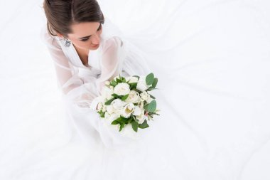 overhead view of young bride in dress holding wedding bouquet, isolated on white