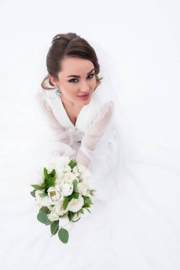 smiling bride in traditional white dress holding wedding bouquet, isolated on white