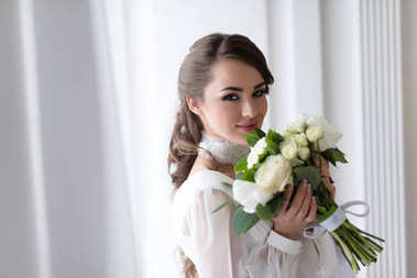 elegant smiling bride with wedding bouquet