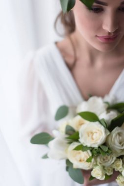 selective focus of young elegant bride with wedding bouquet