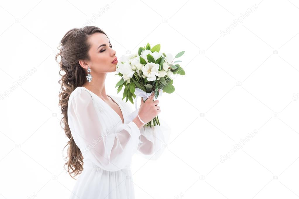 attractive bride in white dress sniffing wedding bouquet, isolated on white