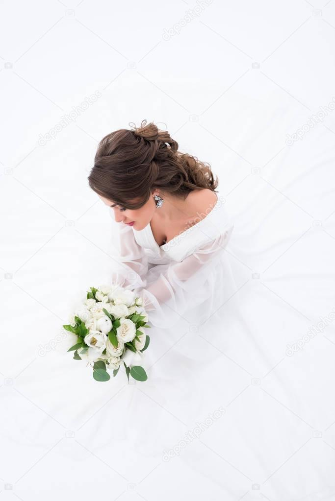 overhead view of elegant bride in traditional dress holding wedding bouquet, isolated on white