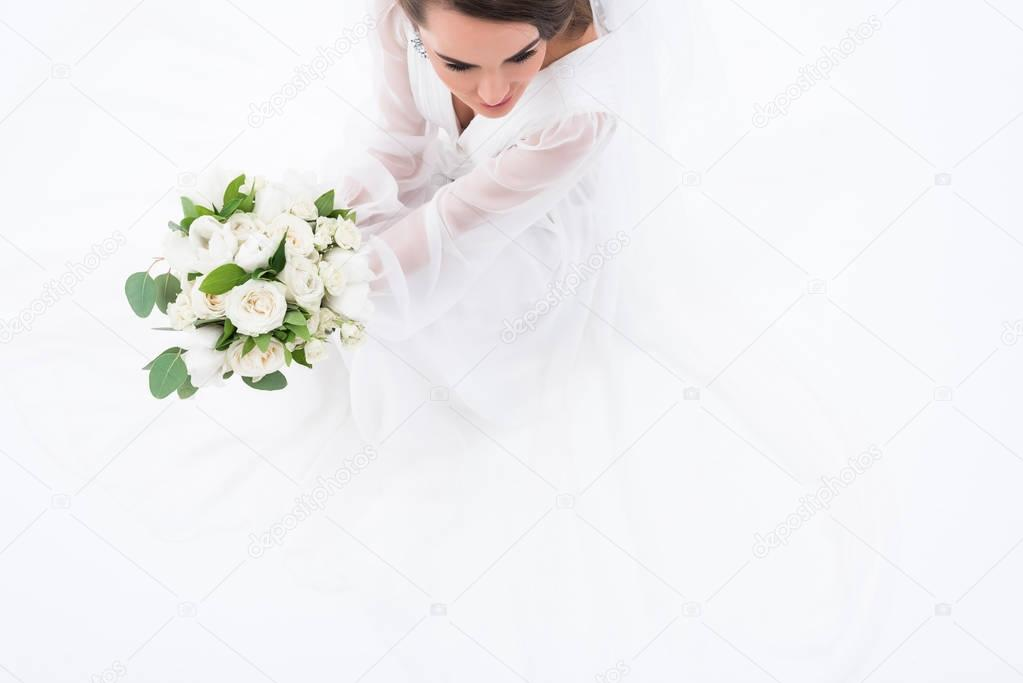overhead view of bride in traditional dress holding wedding bouquet, isolated on white