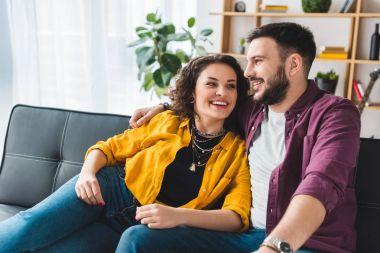 Happy smiling couple sitting on leather sofa