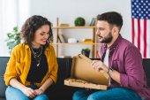 Fotografie Mann mit Pizza Box öffnen und zeigt es seine Freundin