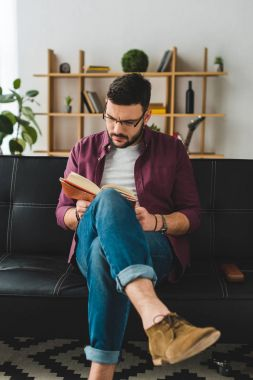Young male in glasses sitting on leather couch and reading book