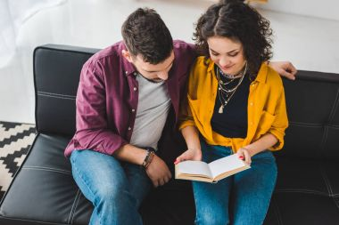 High angle view of young couple sitting on couch and reading book