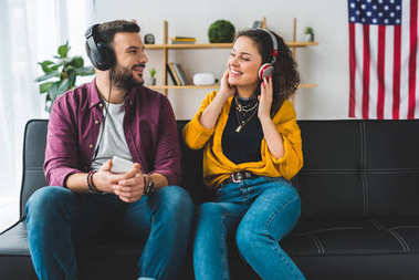 Young couple listening music in headphones and sitting on couch