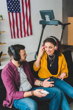 View of couple listening music in headphones and sitting on couch