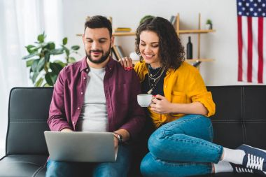 Man using laptop while woman holding cup of coffee