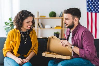Man opening box with pizza and showing it to his girlfriend