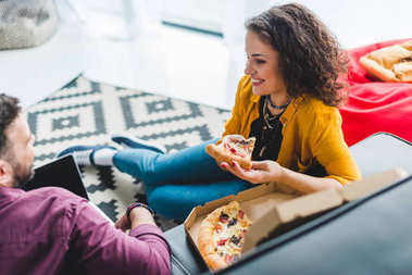 Side view of couple eating pizza and sitting on couch