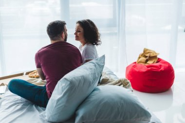 Rear view of young couple sitting on bed with pizza box