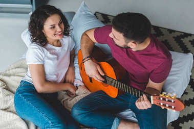 Man plaiyng on acoustic guitar with girlfriend lying beside