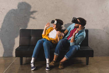 Shadow on wall and couple having fun while using virtual reality headset