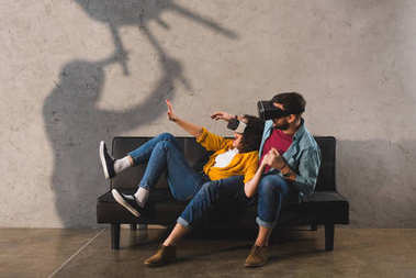 scary shadow holding chair and scared couple in virtual reality headset on couch