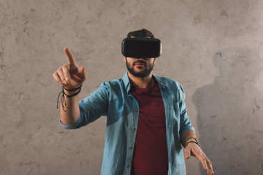 Man using virtual reality headset and pointing by finger