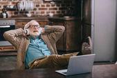 Fotografie glücklicher alter Mann mit Kopfhörer und Laptop mit Füßen auf dem Tisch