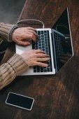 Nahaufnahme der Hände eines älteren Mannes mit Laptop
