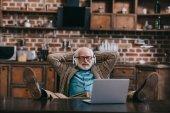 Fotografie Entspannter alter Mann mit Kopfhörer und Laptop mit Füßen auf dem Tisch