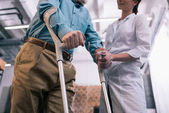 Fotografie Old man leaning on crutches and female doctor hand