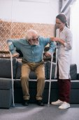 Fotografie Doctor helping senior patient with crutches