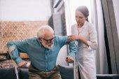 Fotografie Doctor holding old male patient with crutches