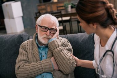 Depressed senior man looking at female doctor