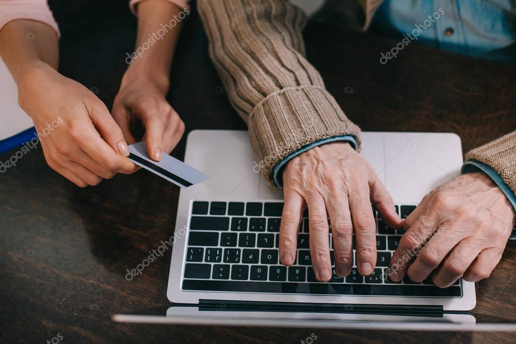 Close-up view of woman and elder man using laptop and credit card