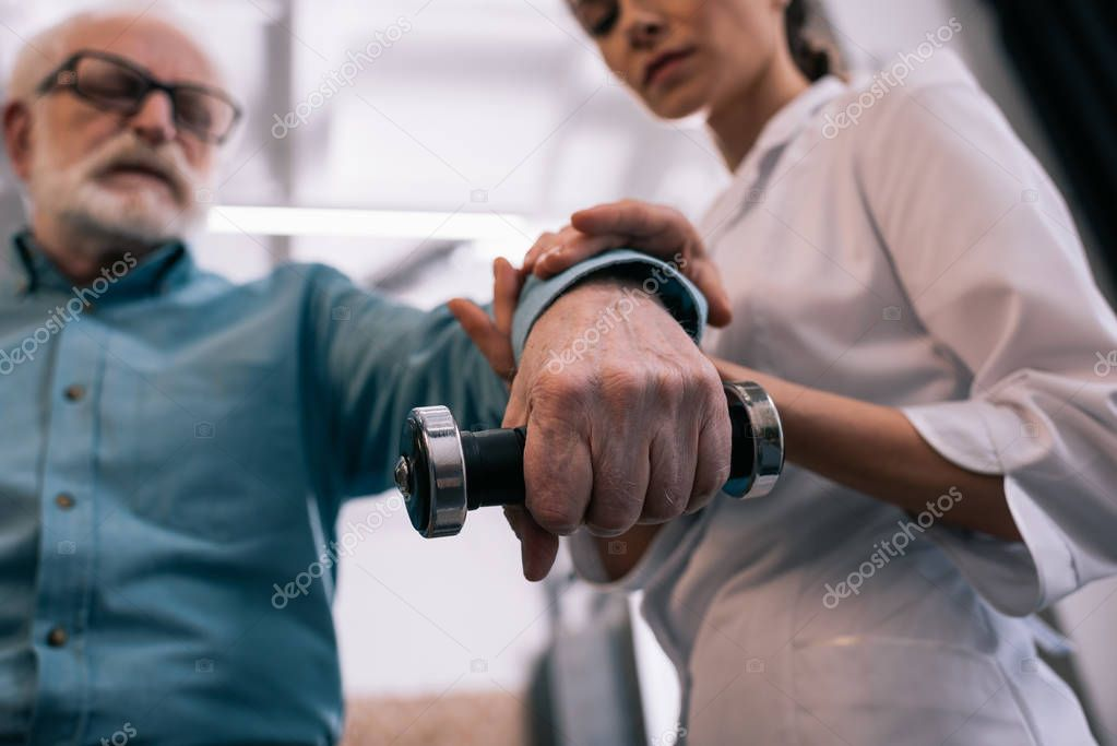 Close-up view of doctor holding senior man hand with dumbbell