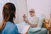 Uomo anziano paziente e infermiera discutendo la trama del libro