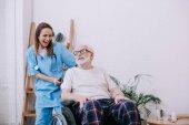 Fotografie Lachende Krankenschwester und Seniorin im Rollstuhl