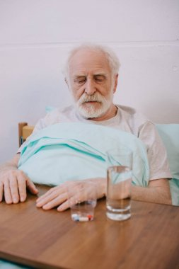 Old man looking sadly at pills on table