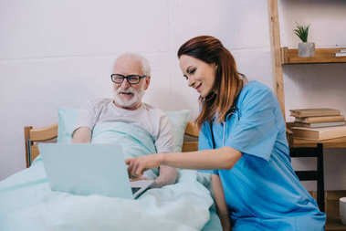 Nurse pointing at laptop in senior patient hands