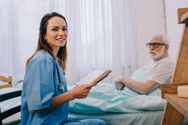 Nurse and senior man reading book