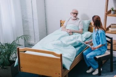 Old man patient and nurse discussing news from newspaper