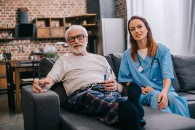 Senior patient with pills and nurse sitting on sofa