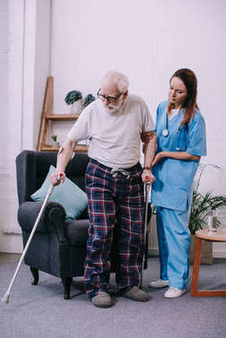 Nurse supporting male patient with crutches