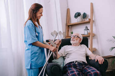 Nurse giving crutches to senior male patient