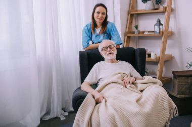 Smiling female nurse standing behind senior man in chair