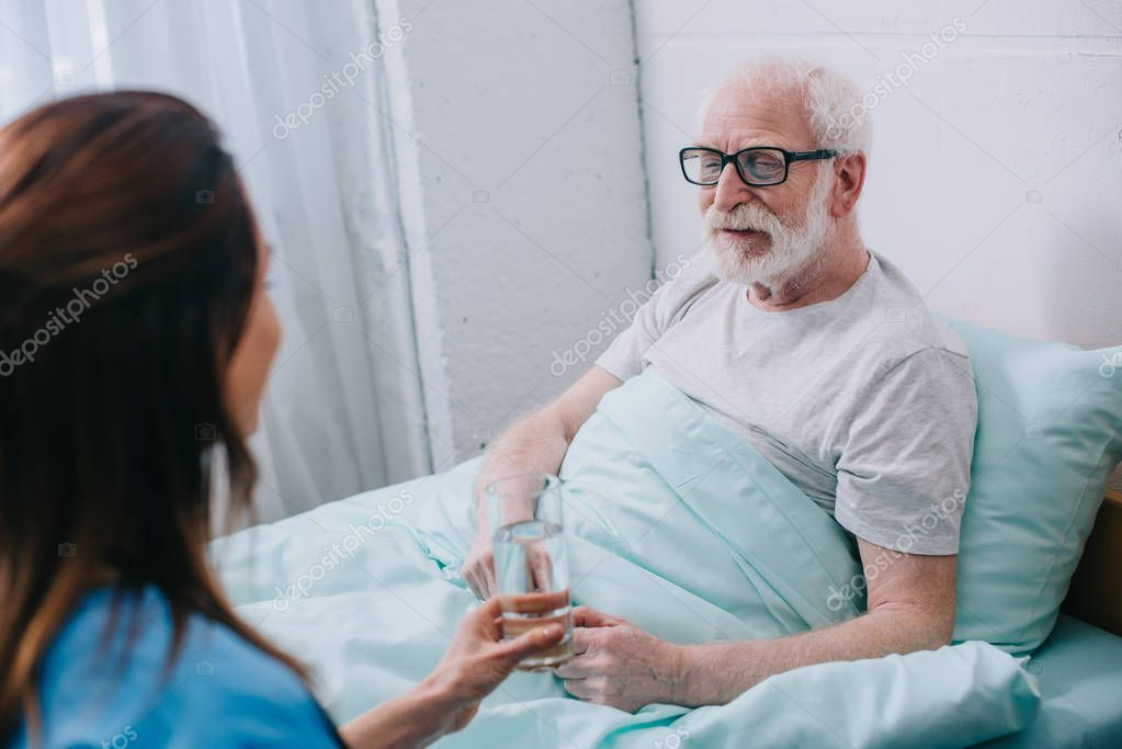 Nurse giving old man in bed a glass of water