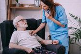 Fotografia Infermiera con lo stetoscopio controllando la frequenza cardiaca del paziente senior