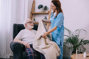 Nurse covering senior patient with plaid