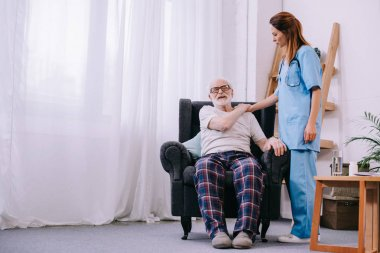 Female caregiver supporting senior man patient