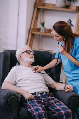 Nurse with stethoscope checking heartbeat of senior man