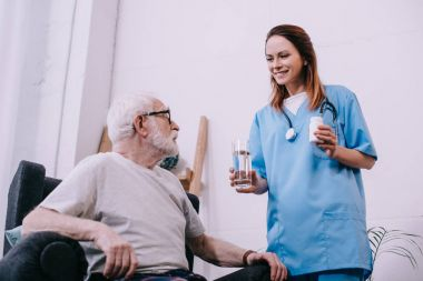 Nurse standing by senior man taking medications stock vector