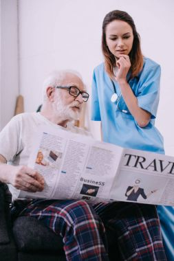 Nurse standing by senior man reading newspaper