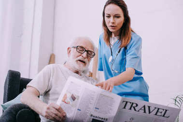Nurse and senior man reading newspaper