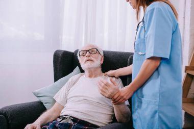 Nurse checking heartbeat of senior man stock vector